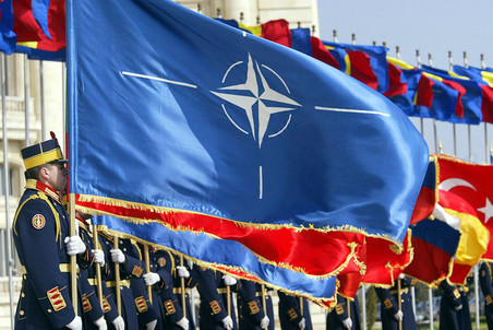 BUCHAREST, ROMANIA:  Romanian army soldiers from the guard regiment holds NATO membership countries flags during the ceremony of NATO flag raising in Bucharest , 02 April 2004. NATO on Monday signed up seven new countries in Eastern Europe in a historic expansion that takes its military muscle to the Russian border. The prime ministers of Bulgaria, Estonia, Latvia, Lithuania, Romania, Slovakia and Slovenia deposited 'instruments of accession' to the North Atlantic Treaty Organization's founding Washington treaty and brought the number of members to 26. Romanian authorities declare national holiday on Friday 2 April 2004 as the Romanian flag will be raised at NATO headquarter in Brussels. AFP PHOTO DANIEL MIHAILESCU  (Photo credit should read DANIEL MIHAILESCU/AFP/Getty Images)